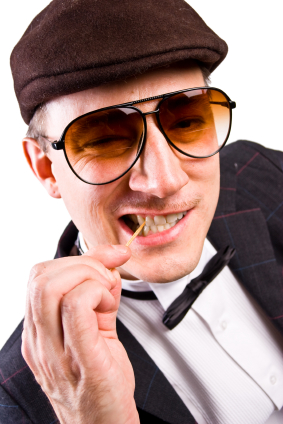 A man with glasses chewing onto a toothpick.