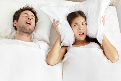 A man snoring loudly and keeping his wife awake.